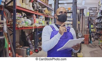 Latin American warehouse worker wearing protective mask making notes during inventory of building materials. Concept of health protection during coronavirus pandemic