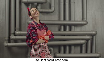 Confident housewife posing with arms crossed in gloves