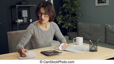 Confident housewife using calculator for checking bills - ...