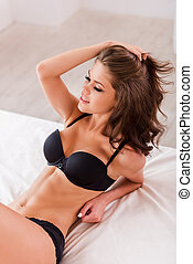 Confident in her beauty. Top view of beautiful young brown hair woman in black lingerie sitting in bed and looking at you