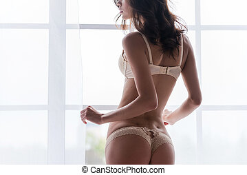 Confident in her perfect body. Rear view of beautiful young woman in lingerie standing near the window and looking away