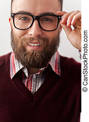 Confident in his handsome look. Close up image  of handsome young man in smart casual adjusting his sunglasses