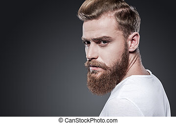 Confident in his look. Thoughtful young bearded man looking over shoulder while standing against grey background