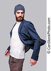 Confident in his perfect look. Handsome young bearded man adjusting his jacket and looking over shoulder while standing against grey background