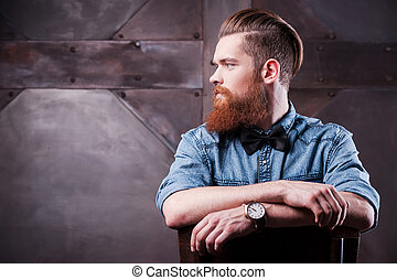 Confident in his perfect style. Profile of a handsome young bearded man looking away and sitting on chair