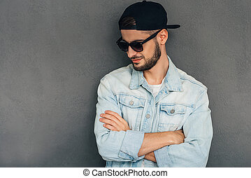 Confident in his style. Confident young man keeping arms crossed and looking down while standing against grey background