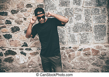 Confident in his style. Handsome young African man in casual clothes adjusting his sunglasses while standing against the stoned wall outdoors