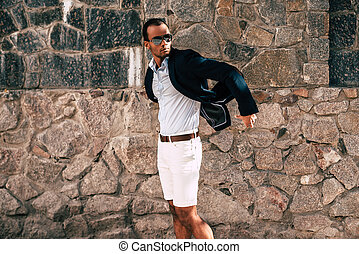 Confident in his style. Handsome young African man in fashionable smart casual clothes posing against the stoned wall outdoors