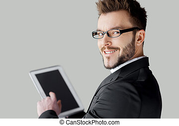 Confident in his tablet. Rear view of cheerful young man in formalwear and glasses working on digital tablet and looking over shoulder while standing against grey background