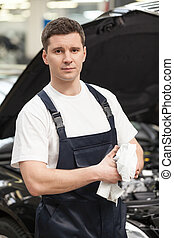 Confident in his work. Close-up of mechanic wiping his hands with handkerchief while standing in front of the car