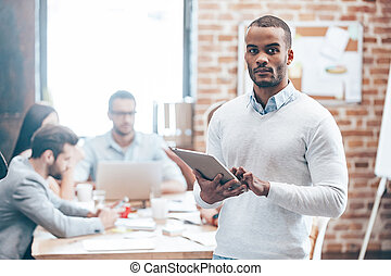 Confident in my team. Young handsome African man holding digital tablet and looking at camera while his colleagues discussing something in the background
