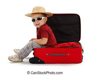 Confident little boy wearing straw hat, sitting in suitcase