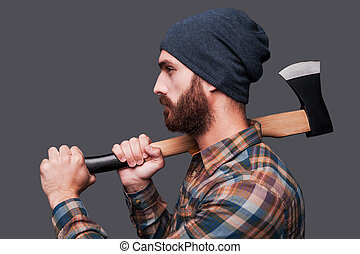 Confident lumberjack. Side view of confident young bearded man holding a big axe and looking at camera while standing against grey background