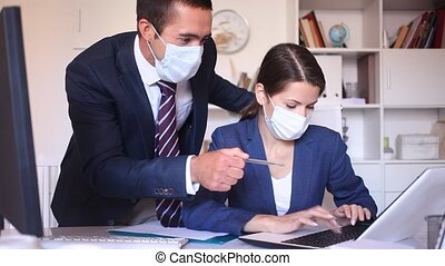 Confident male and female business partners wearing protective masks working in office. New standards due to coronavirus outbreak