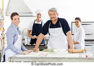Confident Male And Female Chefs Preparing Pasta At Kitchen