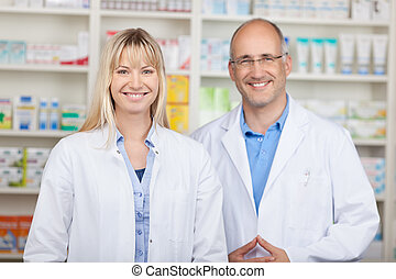 Confident Male And Female Pharmacists Standing In Pharmacy -...