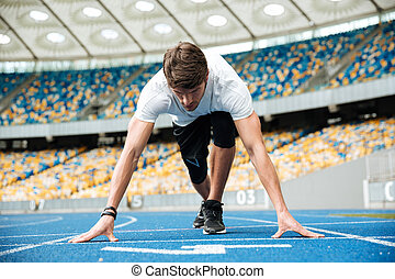 Confident male athlete standing in starting position ready for running