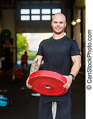 Confident Male Athlete With Weightlifting Plate