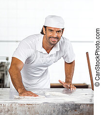 Confident Male Baker Cleaning Flour From Table
