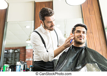 Confident Male Barber Styling Client's Beard In Shop