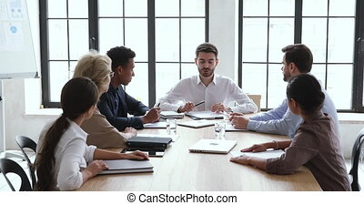 Confident male boss leader instructing interested concentrated multiracial older and younger employees coworkers about project, economic marketing growth strategy at brainstorming meeting in office.