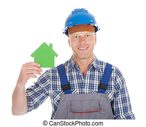 Portrait of confident young male builder holding green house model over white background