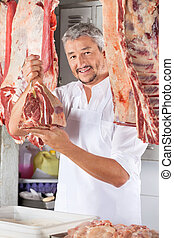 Confident Male Butcher Holding Raw Meat