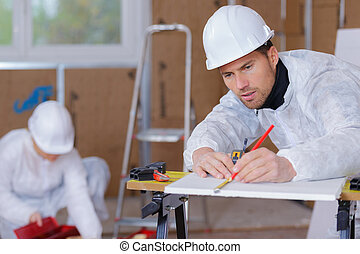 confident male carpenter measuring wooden plank in workshop