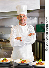 Confident male chef with cooked food in kitchen - Portrait...