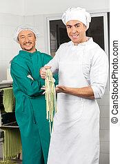 Confident Male Chefs With Fresh Spaghetti Pasta At Kitchen