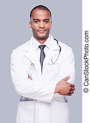 Confident male doctor. Confident African doctor looking at camera and keeping arms crossed while standing against grey background