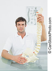Confident male doctor holding skeleton model