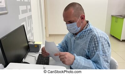 Confident male doctor in medical mask at his workplace in clinic.