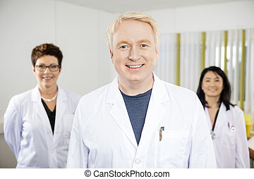 Confident Male Doctor Standing With Colleagues