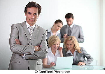 Confident male executive with his team of colleagues in the background