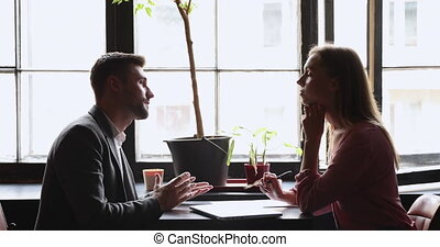 Confident male job seeker talk to female employer recruiter hr manager interviewing applicant listen to vacancy candidate introduce explain qualification work experience at meeting, recruit concept