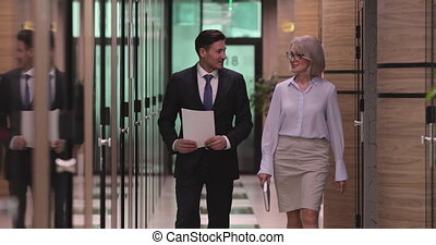 Confident male manager walking in corridor with 60s female ...