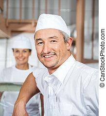 Confident Male Mature Butcher Smiling At Butchery