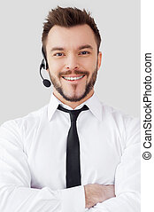 Confident male operator. Handsome young man in formalwear and headset looking at camera and smiling while standing against grey background