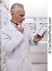 Confident male pharmacist reading instruction