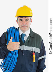 Confident male repairman with rolled wire and hardhat