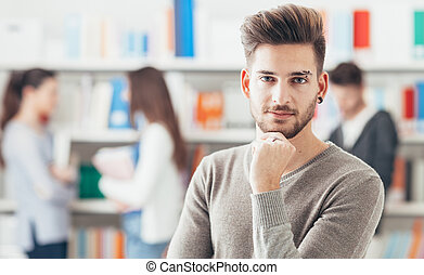 Confident male student posing in the library