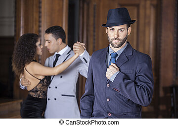 Confident Male Tango Dancer With Partners Performing In Backgrou