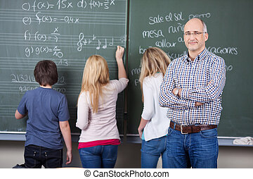 Confident Male Teacher With Students Writing On Blackboard