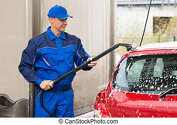 Confident Male Worker Washing Red Car At Garage