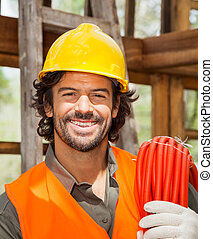 Confident Male Worker With Pipe At Construction Site