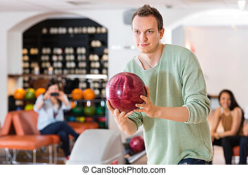 Confident Man Bowling in Club - Young confident man bowling...