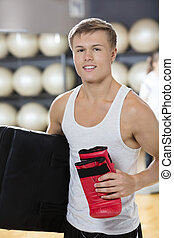 Confident Man Carrying Boxing Glove And Bag In Gym