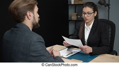 Confident bearded man in trendy suit giving his resume to female hr manager while sitting at wooden table. Interviewer reading cv form to analyse future employee.