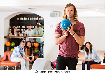 Confident Man Holding Bowling Ball in Club